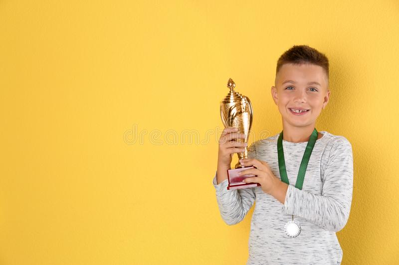 Happy boy with golden winning cup and medal. Space for text. Happy boy with golden winning cup and medal on yellow background. Space for text stock images