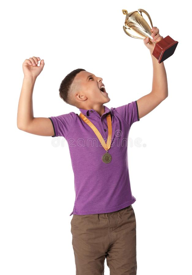 Happy boy with golden winning cup and medal on white. Background stock image