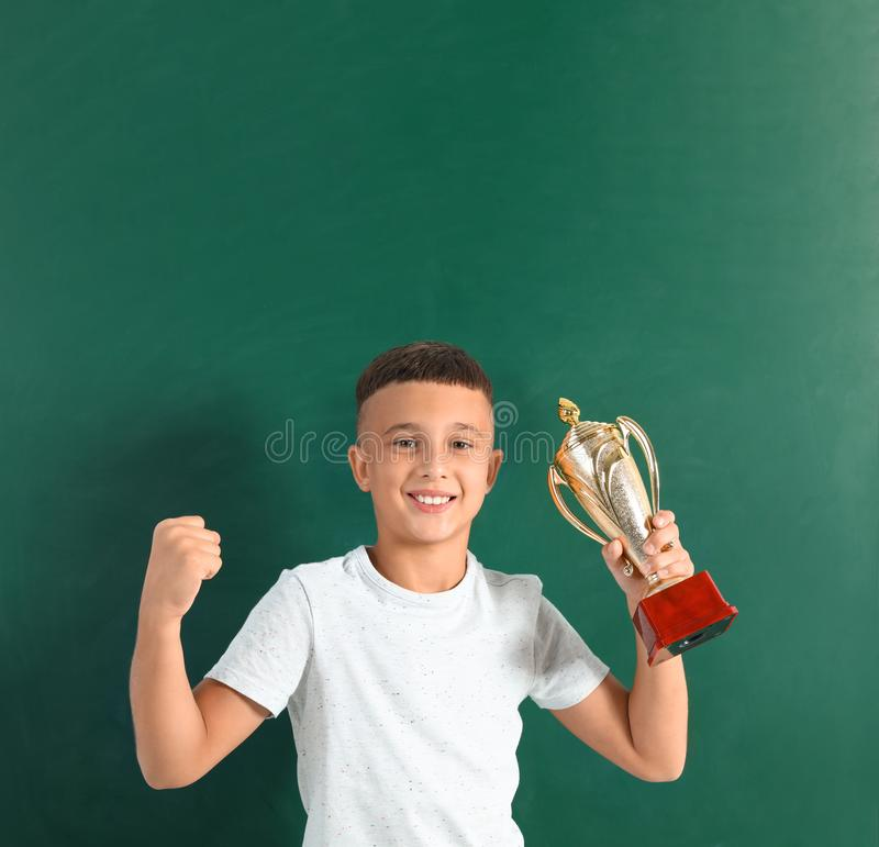 Happy boy with golden winning cup on. Near chalkboard stock images