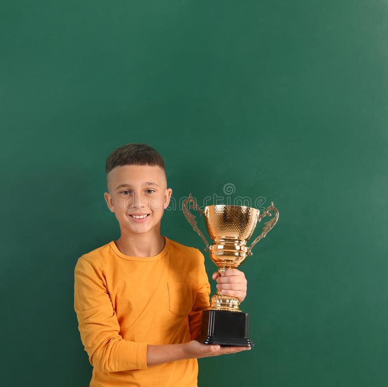 Happy boy with golden winning cup on. Near chalkboard royalty free stock photo