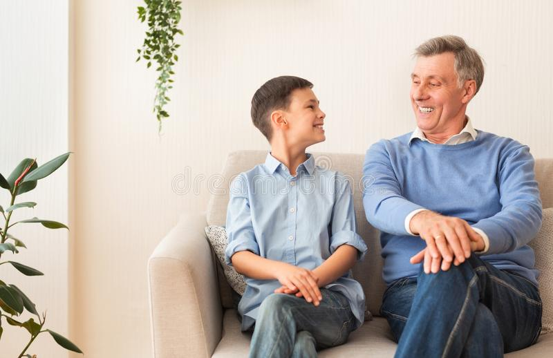 Happy Boy And Grandfather Sitting On Sofa At Home stock image