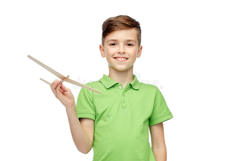 Happy boy in green polo t-shirt with toy airplane royalty free stock photo