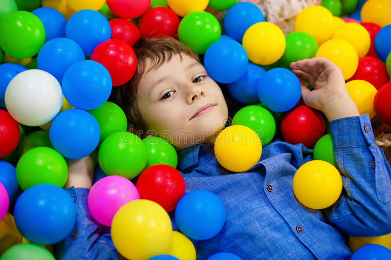 Happy boy having fun in ball pit on birthday party in kids amusement park and indoor play center. Child playing with stock photography