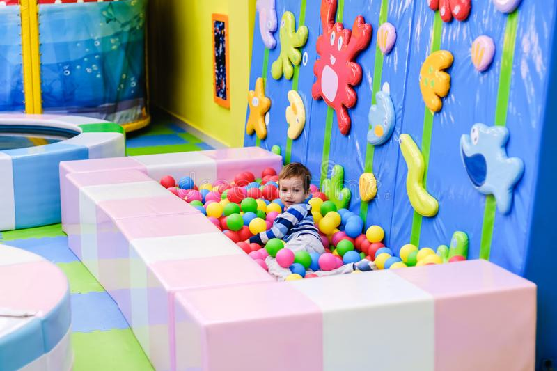 Happy boy having fun in ball pit in kids amusement park and indoor play center. Child playing with colorful balls in playground stock photos