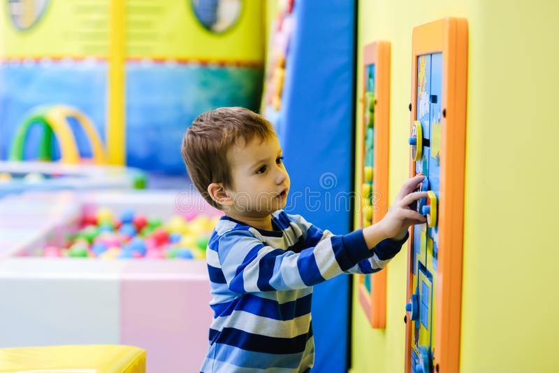 Happy boy having fun in ball pit in kids amusement park and indoor play center. Child playing with colorful balls in playground royalty free stock photography