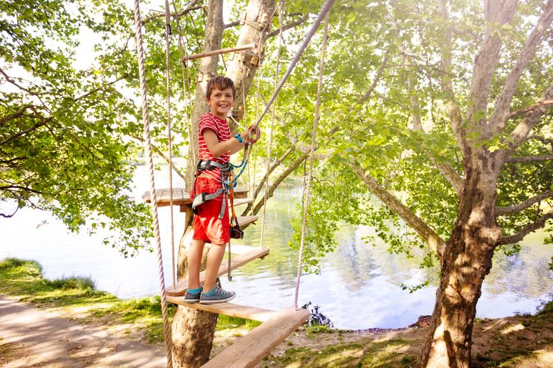 Happy boy have fun on rope walk at adventure park royalty free stock photo