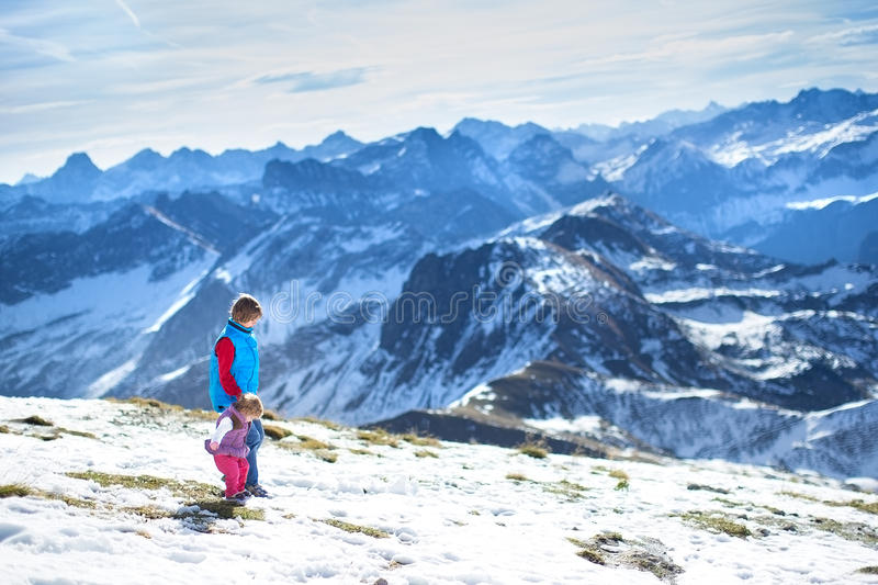 Happy Boy With His Baby Sister In Snow Mountains Stock Photo
