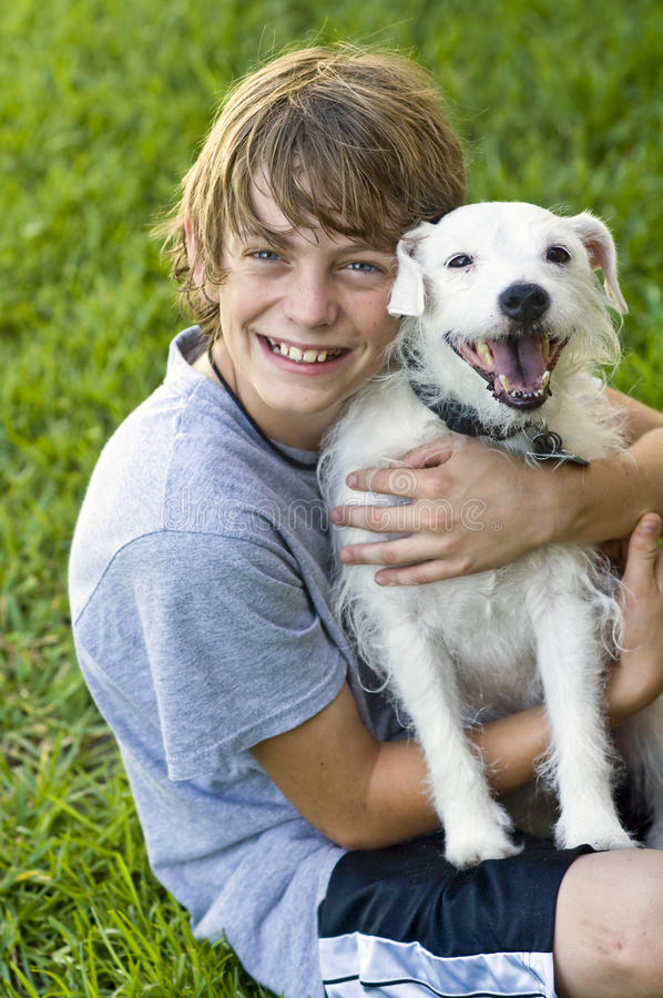Happy Boy and his dog. A smiling 12 year old boy holding his dog in the grass