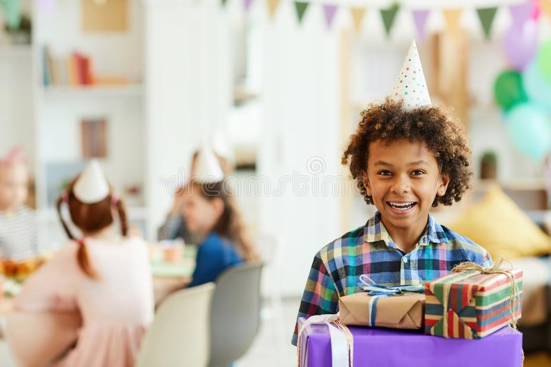 Happy Boy Holding Birthday Presents. Portrait of happy African-American boy holding gift boxes posing during birthday party with friends, copy space stock photos