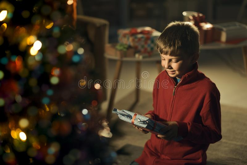 Happy boy holding a Christmas gift royalty free stock image