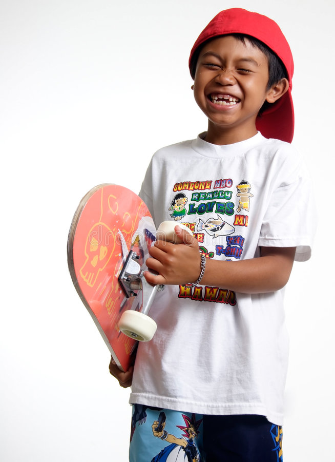 Happy boy holding his skateboard stock image