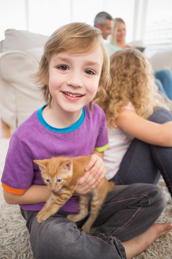 Happy boy holding kitten while sitting with family. Portrait of happy boy holding kitten while sitting with family in living room stock images