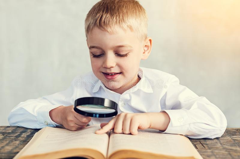 Happy boy holding a magnifying glass while reading stock photo