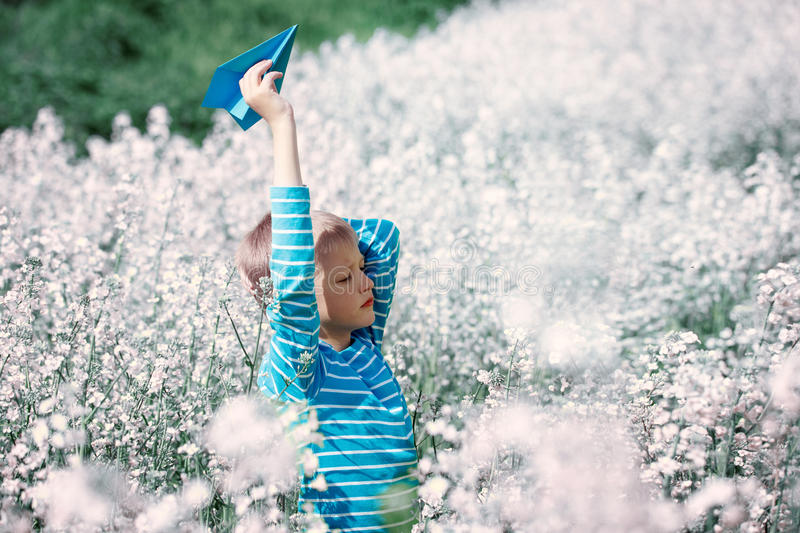 Happy boy holds in hand blue paper airplane on bright sunny day royalty free stock photography