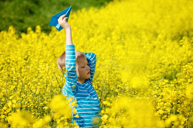 Happy boy holds in hand blue paper airplane on bright sunny day royalty free stock photo