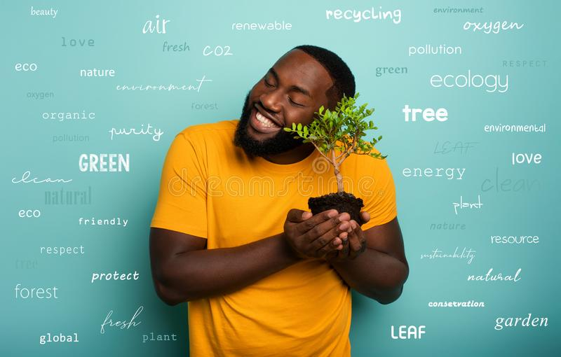 Happy boy hugs a small tree ready to be planted over a light blue color. Concept of forestation, ecology and. Happy black boy hugs a small tree ready to be royalty free stock image
