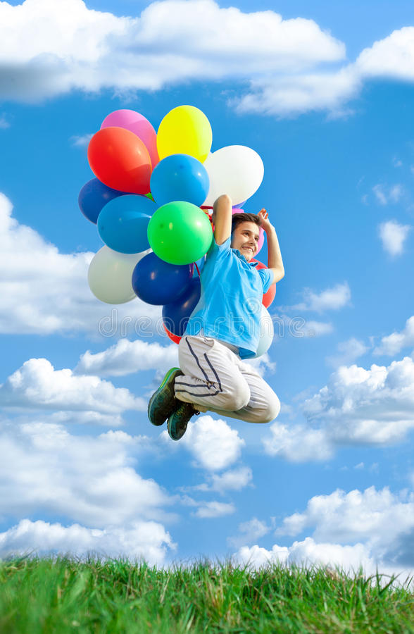 Happy boy jump on meadow with colorfull balloons against blue sk. Happy child playing with colorful toy balloons outdoors stock photo