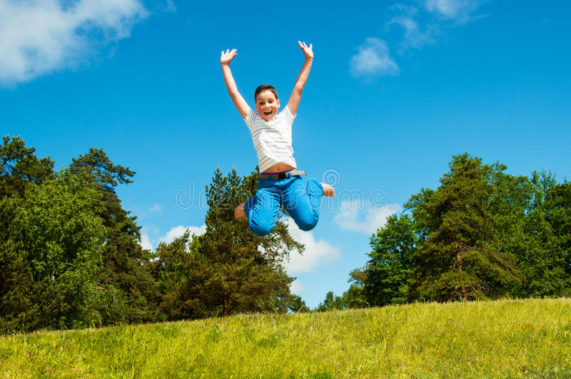 Happy boy jumping outdoors royalty free stock photo