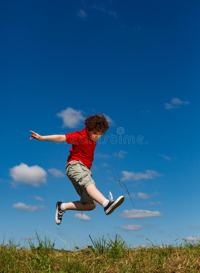 Boy jumping, running against blue sky. Happy boy jumping, running against blue sky stock image