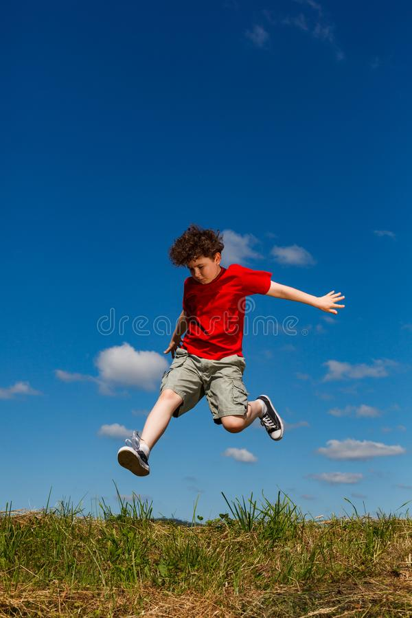 Boy jumping, running against blue sky royalty free stock images