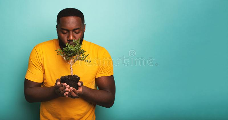 Happy boy kisses a small tree ready to be planted. Concept of forestation. Happy black boy kisses a small tree ready to be planted. Concept of forestation stock photos