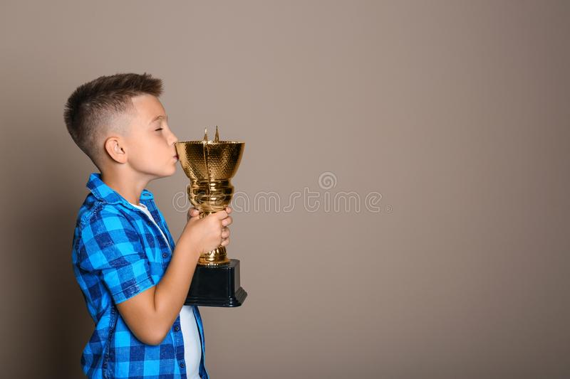 Happy boy kissing golden winning cup on beige background. Space for text stock photo