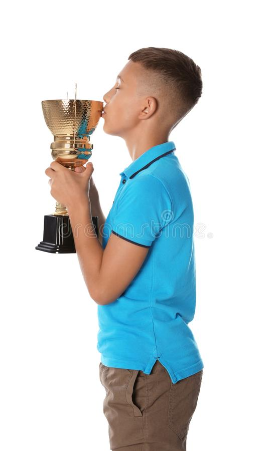 Happy boy kissing golden winning cup on white. Background royalty free stock photography