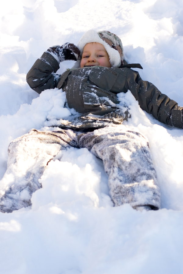 Happy Boy Laying in Fresh Snow stock photography