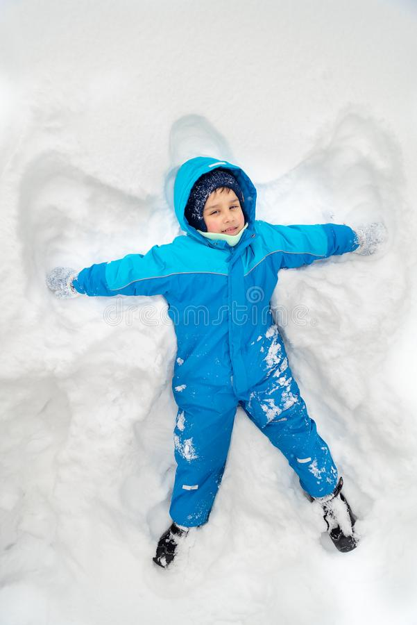 Happy boy laying on snow and making snow angel. Boy have fun. And play with snow outdoors in winter nature. Children in winter day. childhood, leisure and royalty free stock photography