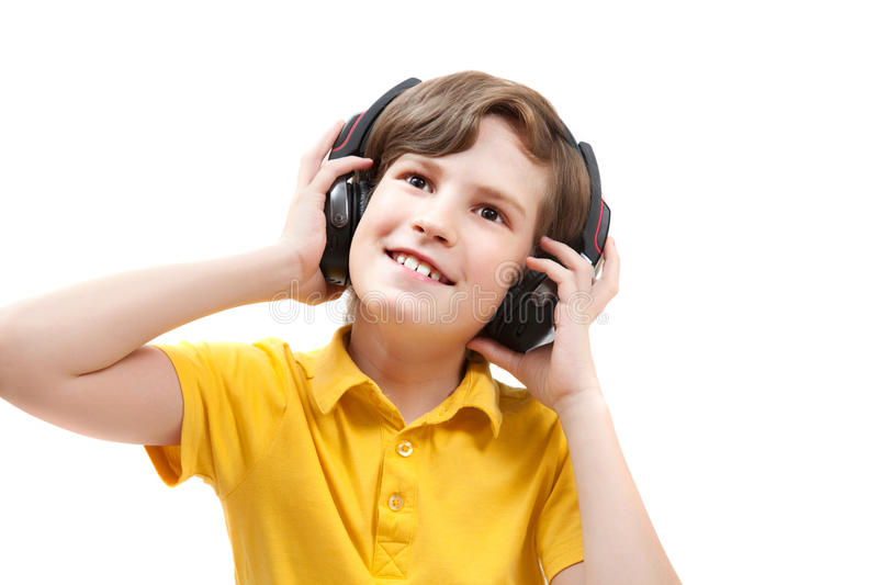 Happy boy listens music with headphones. Isolated on white stock image