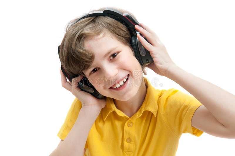 Happy boy listens music with headphones. Isolated on white background stock images