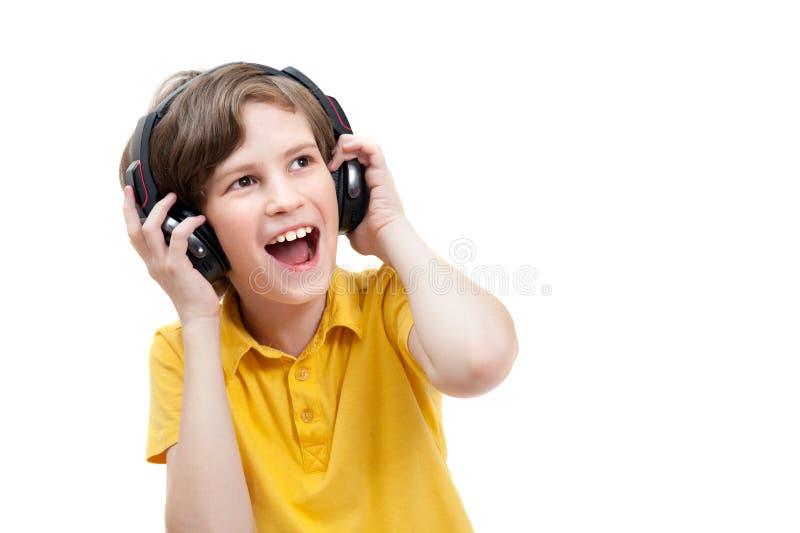 Happy boy listens music with modern headphones. Happy boy listens music, isolated on white royalty free stock image