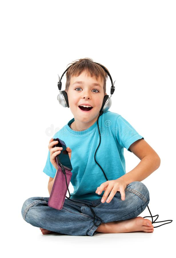 Happy boy listens music with smartphone. Isolated on white stock images