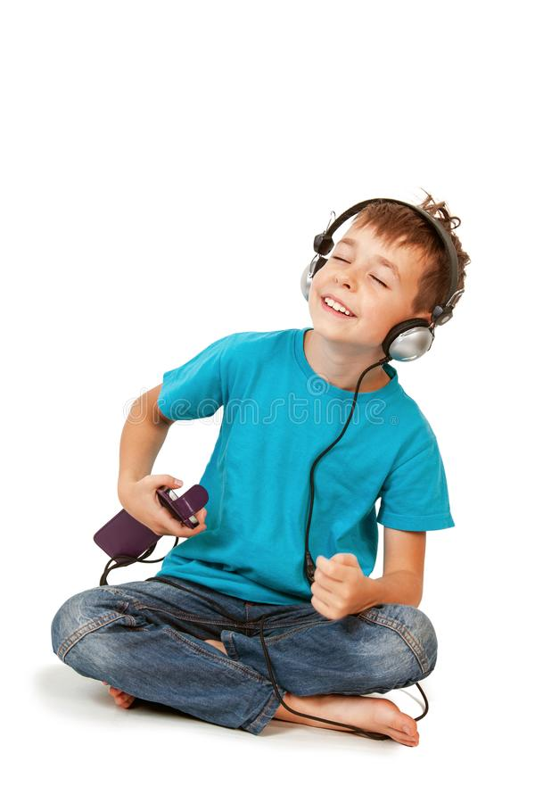 Happy boy listens music with smartphone. Isolated on white royalty free stock photography