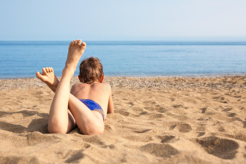 Happy boy lying on the beach stock images