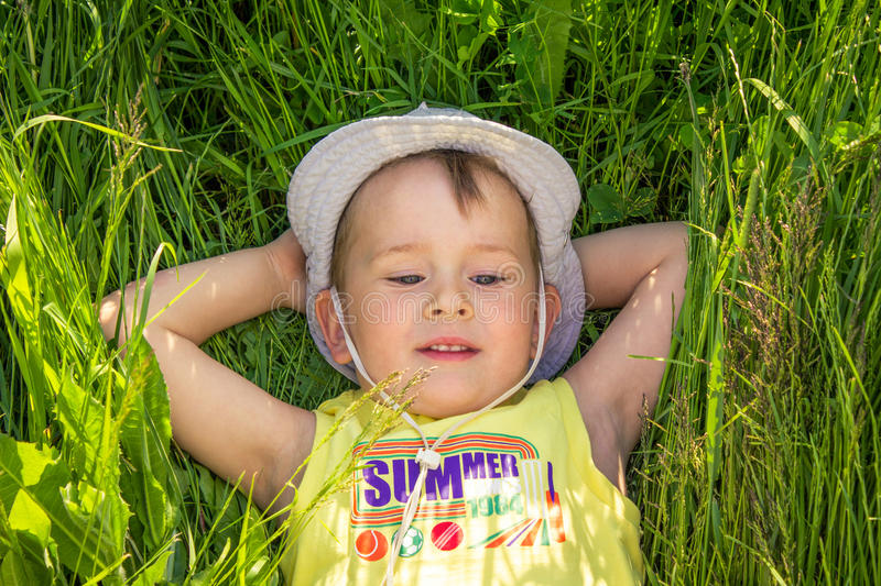 Happy boy. Lying on fresh green grass stock photo