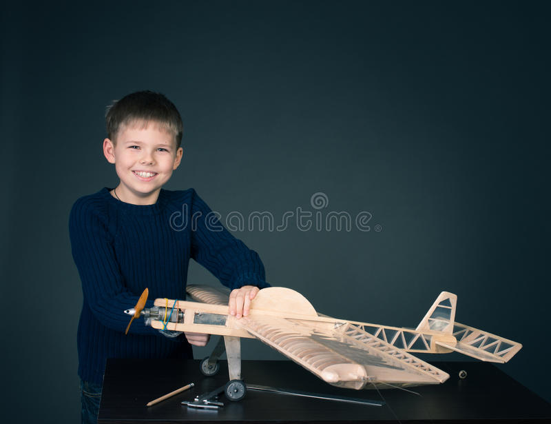 Happy boy with model airplane. Airplane modeling hobby. Plane modeling. Little boy with wooden airplane model stock images