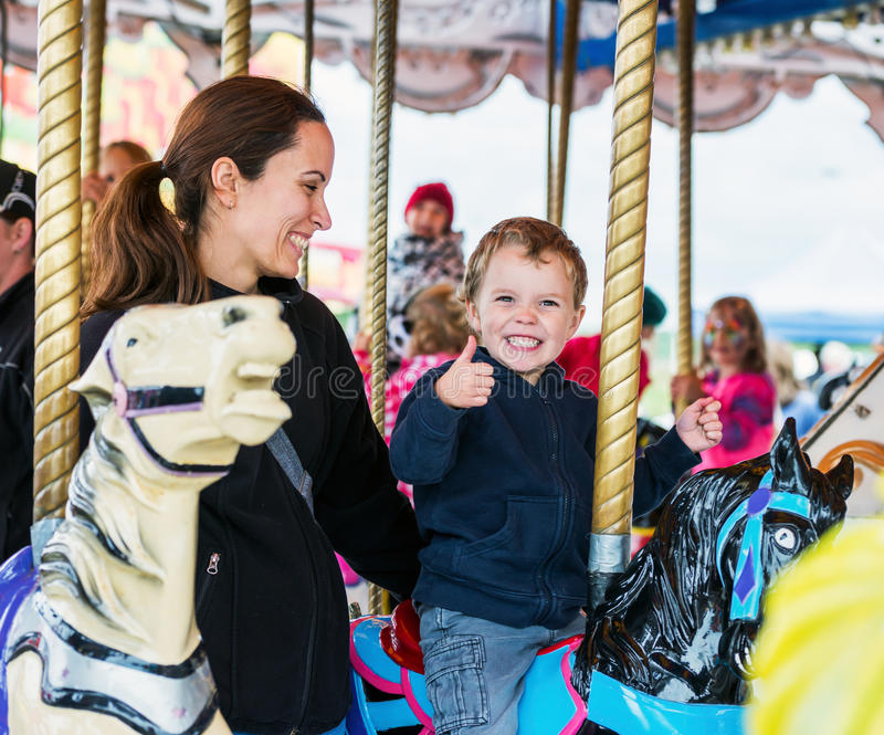 Happy Boy and Mother on Carousel royalty free stock photo