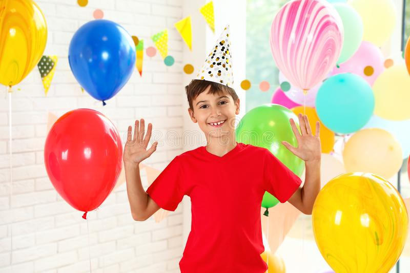 Happy boy near bright balloons at birthday party royalty free stock photography
