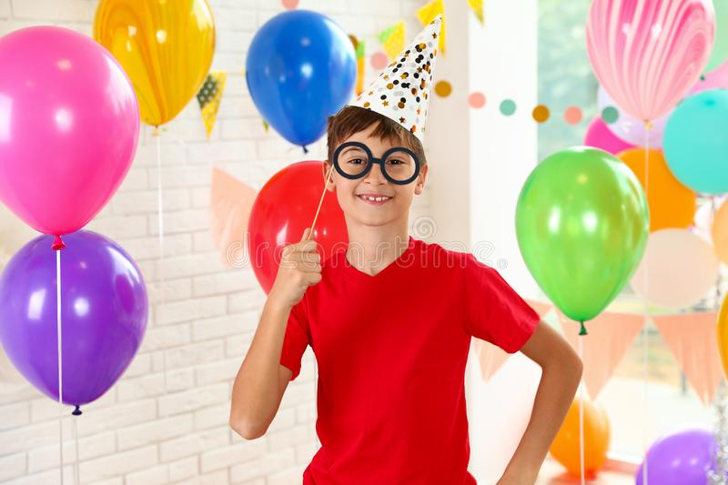 Happy boy near bright balloons at birthday party royalty free stock image