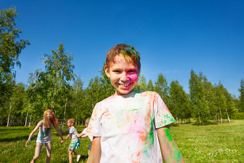 Happy boy painted in colors of Holi festival stock images