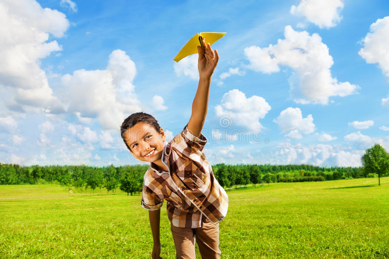 Happy boy with paper plane. Happy boy leaning and throwing yellow paper airplane on bright sunny day in the field stock photo