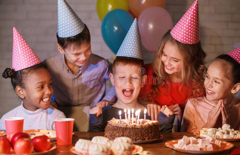 Happy boy in party hat with birthday cake stock photography