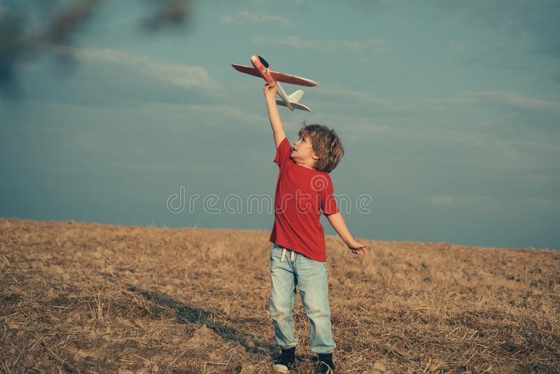 Happy boy play in airplane outdoors. Concept of dreams and travels. Dreams of flying planes. Kids having fun with toy. Airplane in field against blue sky royalty free stock image