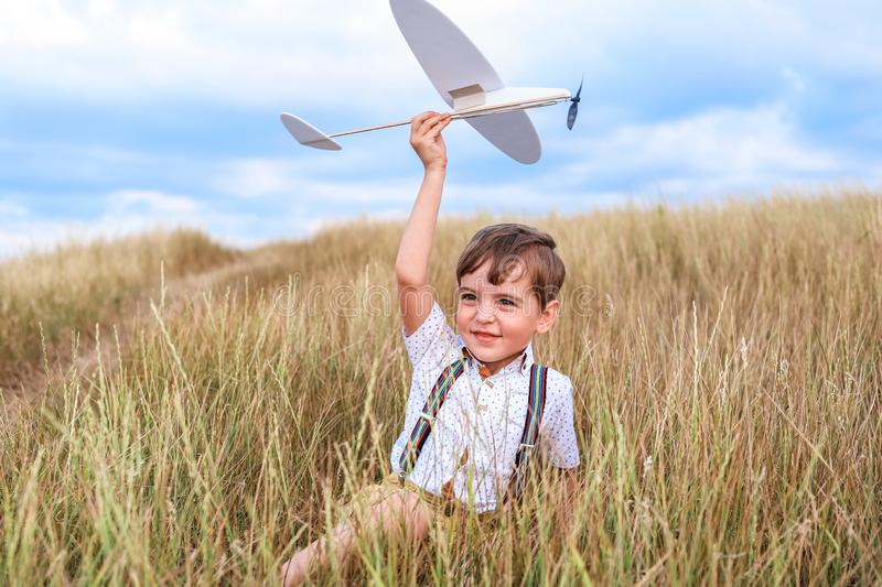 Happy boy play with little white plane. royalty free stock photography