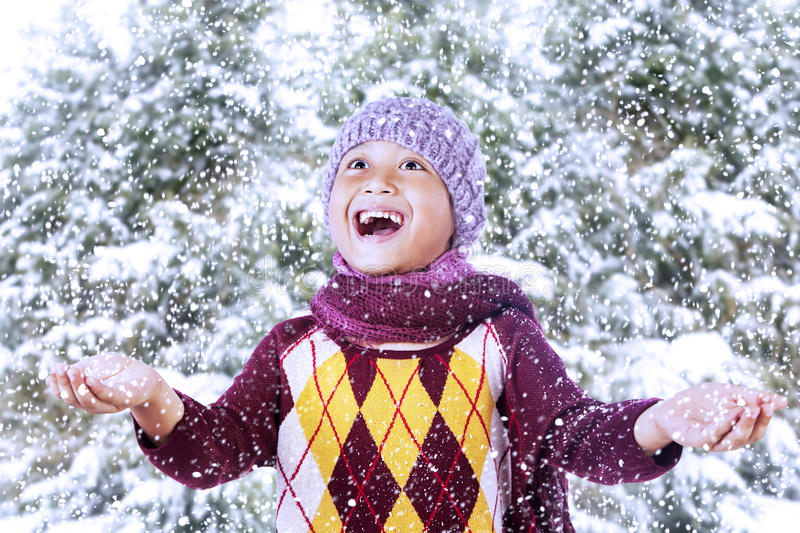 Happy boy play with snow on mountain. A happy boy is playing with snow on the mountain during winter royalty free stock images