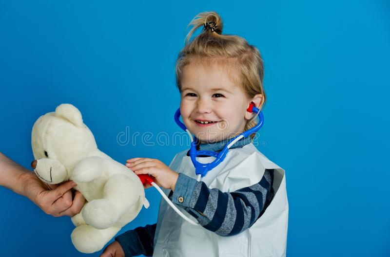 Happy boy play veterinarian with teddy bear in mothers hand. Child vet doctor examine toy pet with stethoscope on blue background. Veterinary clinic game royalty free stock photos