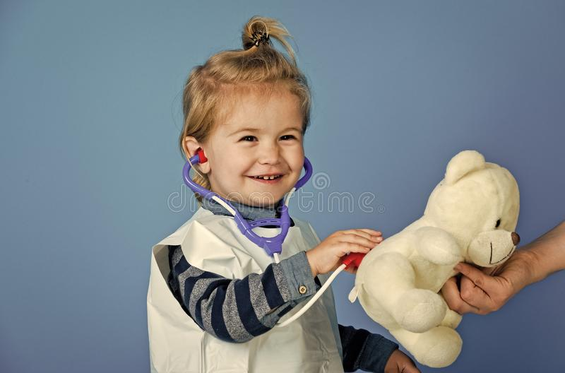 Happy boy play veterinarian with teddy bear in mothers hand. Child vet doctor examine toy pet with stethoscope on blue background. Veterinary clinic game stock photos