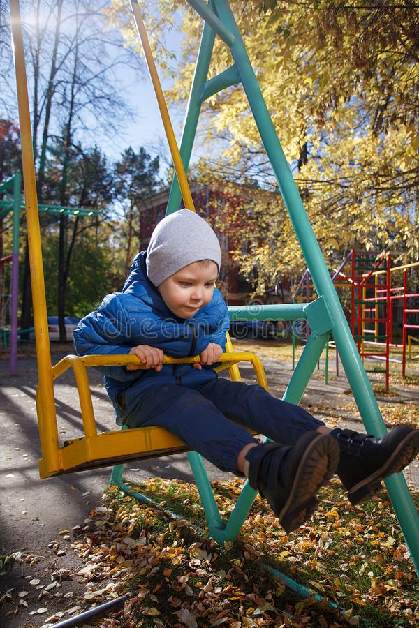 Happy boy playing in the autumn park, funny 4 years old toddler, seasonal walking outdoor, bright color of the weather, sunny day stock images