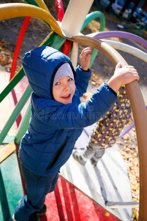 Happy boy playing in the autumn park, funny 4 years old toddler, seasonal walking outdoor, bright color of the weather, sunny day stock photo